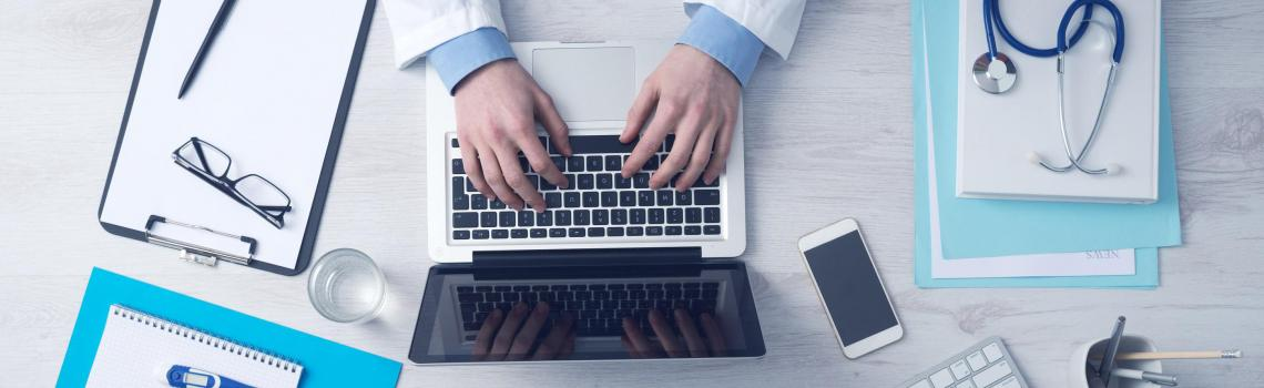 Doctor working on desk with computer